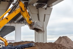 Heavy excavators with hydraulic buckets work under a high reinforced concrete bridge at a construction site to strengthen the bank river