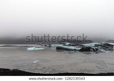 Stock Photo Heavy fog hanging above seascape with icebergs, frozen water and black volcanic soil in extreme and beautiful winter weather conditions and harsh rugged terrain of Icelandic southern glacier