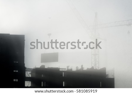 Heavy fog Monochrome image. Crane building construction. workers at a construction site. Black contour. outline in the fog. #581085919