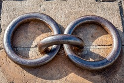 Heavy gauge cast iron rings in close-up view. One ring is anchored into the cobblestone with two rings laying freely on each side. Commonly seen along coastlines and used for mooring boats.