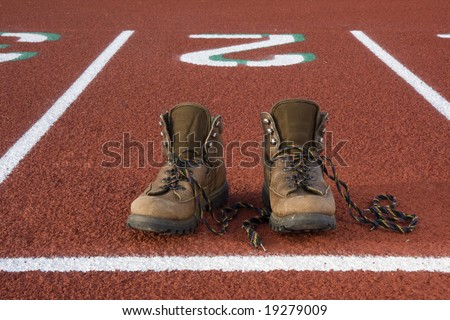 heavy hiking boots at starting line on a running track, concept - wrong equipment for a job