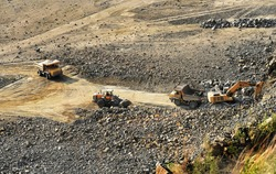 heavy industrial machinery works in a rock loading quarry. A crane loads granite stones in a quarry onto a truck. View from above.
