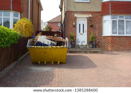 Heavy industrial yellow rubbish skip on driveway. Selective focus on full metal bin with space to add text on area in background, brick house and car park surface. Renovate, moving, clearance concept.