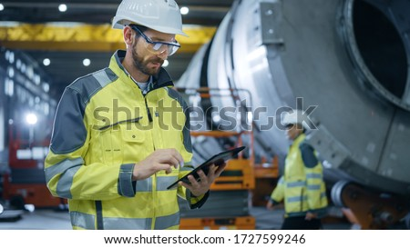 Heavy Industry Engineer Stands in Pipe Manufacturing Factory, Use Digital Tablet Computer. Facility for Construction of Oil, Gas and Fuel Pipeline Transportation Products.