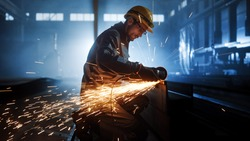 Heavy Industry Engineering Factory Interior with Industrial Worker Using Angle Grinder and Cutting a Metal Tube. Contractor in Safety Uniform and Hard Hat Manufacturing Metal Structures.