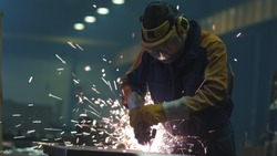Heavy industry worker at a factory is working with metal on a angle grinder while hot sparks are produced in a result.