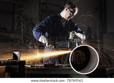 Heavy industry worker cutting steel pipe with angle grinder in workshop. - stock photo