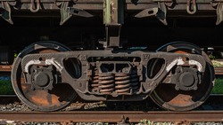 heavy iron wheels and springs of an old wagon locomotive on a railway track with wooden sleepers, standing in an old abandoned train depot