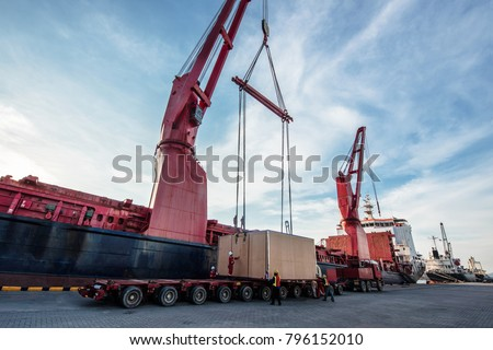 heavy lift cargo handle by the professional teamwork to locate the package from the ship crane onto the center gravity of the lowbase trailer to make sure safety balance carry out in proper safe work