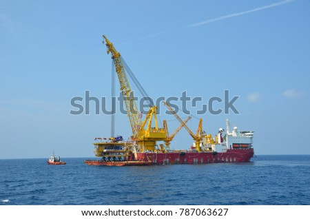 Heavy lift crane of derrick lay vessel hooked on wellhead platform topside ready to lift it off cargo barge.