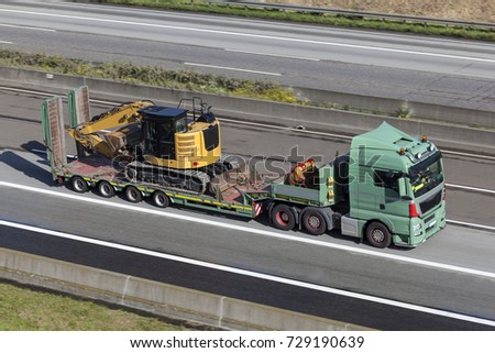 Heavy load truck hauls big excavator on the highway