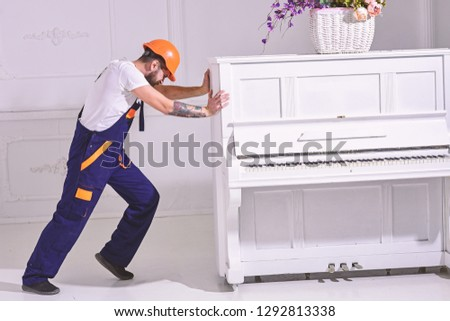 Heavy loads concept. Loader moves piano instrument. Courier delivers furniture, move out, relocation. Man with beard worker in helmet and overalls pushes, put efforts to move piano, white background. #1292813338