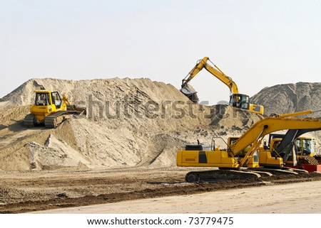 Heavy machinery equipment at road construction site - stock photo
