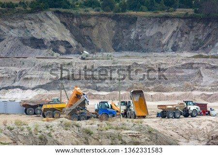 heavy machinery heavy trucks working in a mining quarry