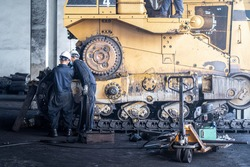 Heavy machinery maintenance and repair, Mechanic man assembly track link of the bulldozer in coal power plant