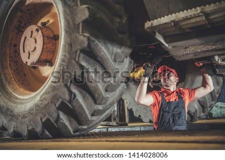 Heavy Machinery Mechanic. Caucasian Technician Under Medium Size Construction Bulldozer.