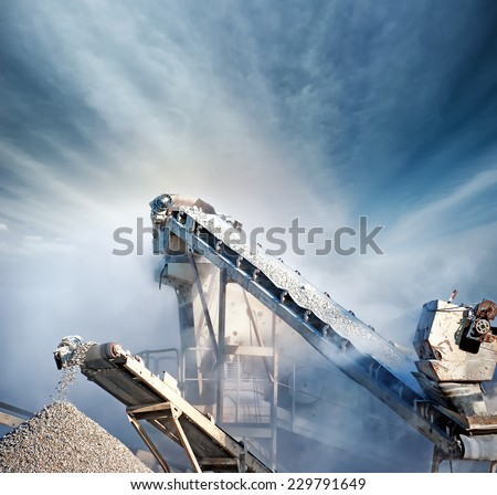 Heavy machinery of gravel production in quarry. Stones breaking factory with pit and moving conveyor belt loading crushed stones