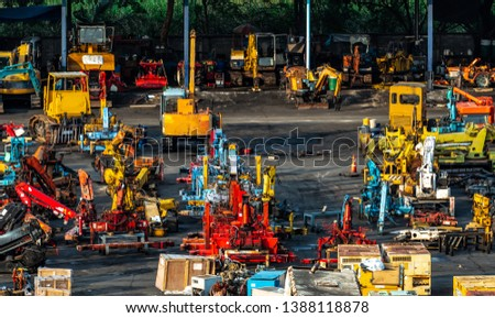 Heavy machinery second hand market. Crane, forklift, backhoe, and electric generator on dirty concrete floor. Warehouse of heavy machinery for manufacturing factory. Low cost heavy machinery.