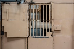 Heavy metal gates with window at the entrance to the prison. Heavy door with locks and bars at the entrance to the corridor with prison cells.