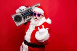 Heavy metal winter noel wish funky mood mature aged senior Nicholas white beard in costume headwear gloves stylish star glasses show tongue out hold vintage record player isolated on red background