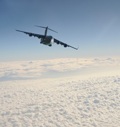 heavy military transport jet above the clouds