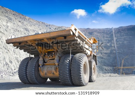 Heavy mining dump truck driving along the opencast Ore conveyor at background