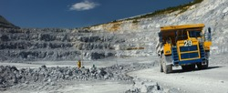 Heavy mining dump truck on the background of a stone quarry close-up, panorama.