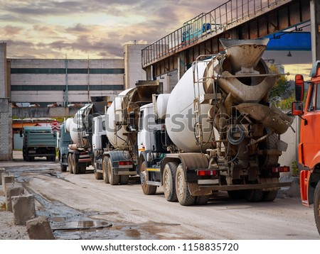 Heavy mixer concrete trucks waiting for to be loaded on the concrete mixing and batching factory. Deficiency of concrete and sand formed a queue for loading at the building materials factory.