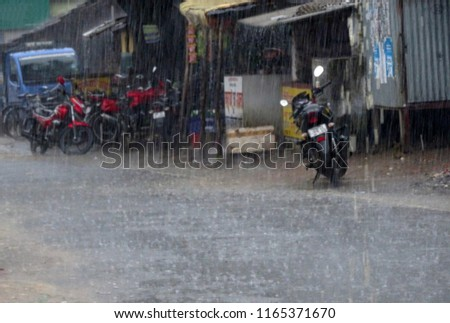 Heavy rain at a highway street path with rain drops , bikes parked near a stall , intentional exposure, blurred photo  #1165371670