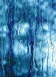 heavy rain drops on blue window