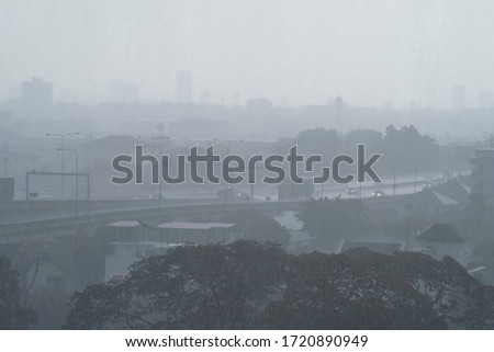 Photo of  Heavy rain showering the city's expressway during rush hour. It's raining heavily in city because of thunder storm. Weather forecast & Heavy rain downpours tollway concept.