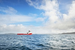 Heavy red lift tug off the coast of North sea, Norway. Freight transportation, nautical wessel, global communications, logistics theme