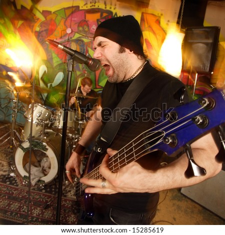 Heavy rock band with bassist and drummer playing. Shot with strobes and slow shutter speed to create lighting atmosphere and blur effects.