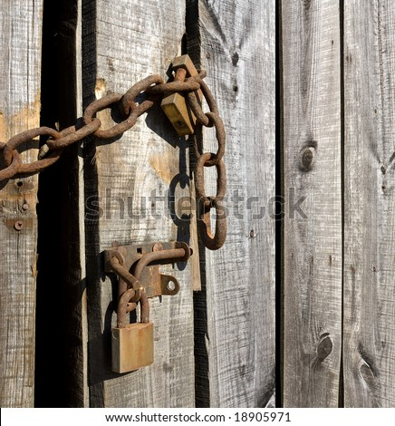 Heavy rusty chains and padlocks on a fragile wooden door.