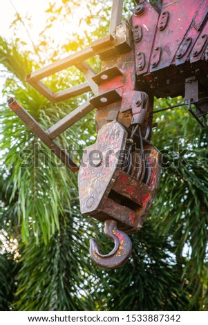 heavy rusty hoist iron hook with beam Girder lifting of machinery crane construction industrial with tree background