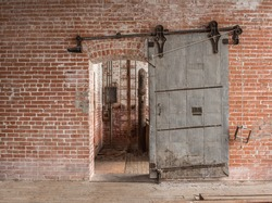 Heavy sliding industrial door in old warehouse with pipes and ladder against a brick wall with wooden floors