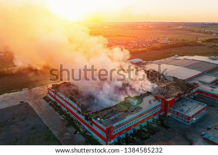 Heavy smoke in burning industrial distribution warehouse or storehouse industrial hangar from burned roof, aerial view of fire disaster