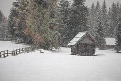 heavy snowfall in mountain village over old wooden hut, Slovenia