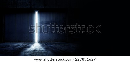 Heavy steel doors opening. Large steel doors of an hanger like building opening and light coming in. with copyspace