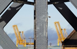 Heavy steel frame with rivets in front of two yellow cranes