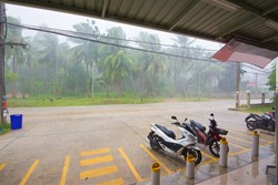 heavy tropical rain with the wind parked near a store on Koh Phangan island in Thailand, a storm in the rainy season