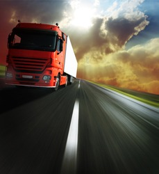 Heavy truck on blurry asphalt road under sunlight