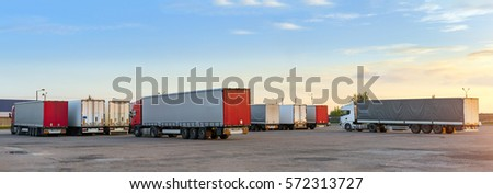 Heavy trucks loaded with goods trailers, parked in waiting area on state border crossing. International hard transportation and logistics. Transport infrastructure in evening at sunset #572313727