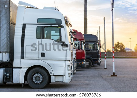 Heavy trucks loaded with goods trailers, parked in waiting area on state border crossing. International hard transportation and logistics. Transport infrastructure in evening at sunset #578073766
