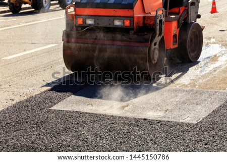 Heavy vibrating roller compacts hot asphalt on the repaired asphalt surface of the carriageway on a clear sunny day #1445150786
