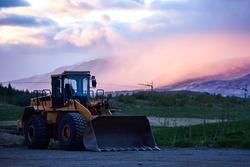 heavy wheel excavator machine at sunset