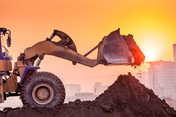 heavy wheel excavator machine working at sunset