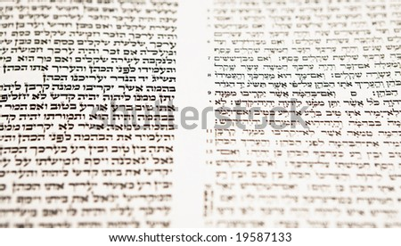 Hebrew text, with selective focus, from a tikkun, which is a book used for Bar Mitzvah study, with modern Hebrew text on the right and the same text, as it appears in a Torah scroll, on the left.