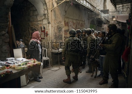HEBRON - MARCH 25: Israeli soldiers guard a procession of Jewish settlers as they march through the old corridors of the religiously-important West Bank city of Hebron, March 25, 2012.