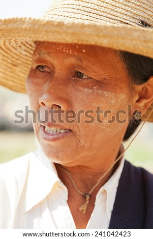 Heho, Myanmar - March 02, 2011 : Burmese woman shot near five day market on Inle Lake, she is wearing a typical hat and facial herb make up called thanaka